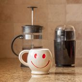 image of taupe  - Brewing a cup of coffee in kitchen with grinder and french press for smile face mug - JPG