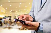 stock photo of restaurant  - Business man using mobile smart phone in Restaurant or Food Court Plaza - JPG