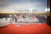 stock photo of inverted  - inverted wine glasses on a red tablecloth - JPG