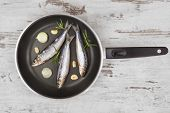 stock photo of cook eating  - Fresh anchovy fish on black pan on white textured wooden background - JPG