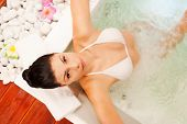 image of hot-tub  - Top view of attractive young woman relaxing in hot tub and looking at camera