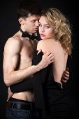 picture of undressing  - Steamy scene after party beautiful young couple caught up in the middle of undressing before sex woman in evening dress looking at camera studio black background - JPG