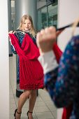 image of mirror  - Woman trying red dress shopping for clothing - JPG