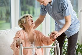 stock photo of physiotherapist  - Disabled woman using walker assisted by physiotherapist - JPG