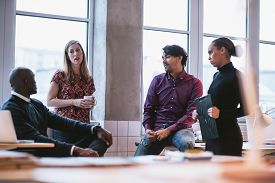 image of coworkers  - Shot of diverse business team discussing work in office. Creative young people discussing new business project. ** Note: Shallow depth of field - JPG
