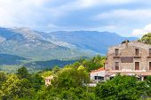 stock photo of stone house  - Rural Corsican landscape old stone houses and mountains on the horizon - JPG