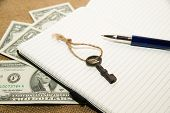 picture of memento  - Opened notebook with a blank sheet pen key and money on the old tissue - JPG