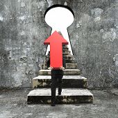 foto of keyhole  - Man carrying red arrow up sign climbing old concrete stairs toward keyhole with blank white view - JPG