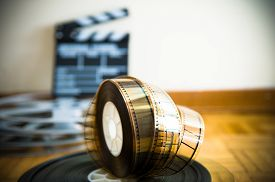 stock photo of clapper board  - 35 mm cinema film reel and out of focus movie clapper board in background on wooden floor - JPG