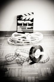 picture of mm  - 35 mm cinema film reel and out of focus movie clapper board in background on wooden floor in vintage black and white vertical frame - JPG