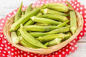 stock photo of okras  - Green okra vegetable on red napkin against white wooden background - JPG