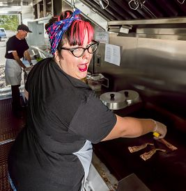 foto of food truck  - Smiling pink haired chef grills bacon in a food truck - JPG
