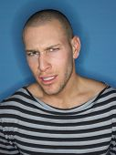 stock photo of shaved head  - Man in stripy top frowning in studio - JPG