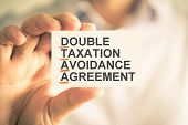 Businessman Holding Card With Dtaa Double Taxation Avoidance Agreement Acronym Text poster