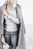 Unrecognizable model wearing casual outfit and holding clutch bag. Gray clothing in trendy minimalis poster