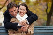 Happy couple using Social Media with a smartphone