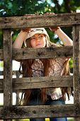 Beautiful cowgirl in stetson looking through fence