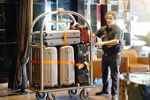 Close-up Many Suitcases On Hotel Luggage Cart Moving By Bell Boy. Baggage Porter Or Bell Boy Bringin poster