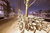 stock photo of covered bridge  - Amsterdam in the Netherlands at night covered with snow - JPG