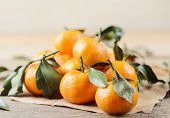 Fresh Juicy Little Tangerines With Green Leaves In A Heap On White Wooden Background And Craft Paper poster