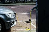 Electric Car Charging On Parking Lot With Electric Car Charging Station On City Street. Electric Car poster