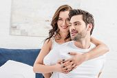 Woman Tenderly Embracing Man And Looking At Camera In Bed poster