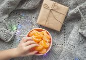 A Child Is Holding Pink Bowl Full Of Peeled Sweet Tangerines On Grey Knitted Background With Wraped  poster