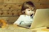 Cute Funny Little Baby Boy With Long Blonde Curly Hair Playing On Computer And Speaking By Mobile Ph poster