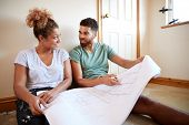 Couple Sitting On Floor Looking At Plans In Empty Room Of New Home poster