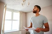 Male First Time Buyer Looking At House Survey In Room To Be Renovated poster