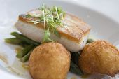 stock photo of dauphin  - Fresh King Fish Fillet on Green Beans Almandine with Dauphine Potatoes presented on a white plate served to perfection - JPG