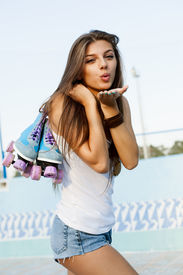 pic of roller-derby  - Photograph of a roller derby girlholding her skates by the laces outdoors - JPG