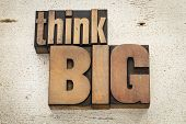 think big - motivation concept in vintage letterpress wood type on a grunge painted barn wood backgr