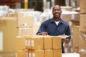 stock photo of warehouse  - Worker In Warehouse Preparing Goods For Dispatch - JPG