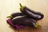 stock photo of aubergines  - Raw aubergines or eggplants on wooden backround - JPG