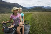 stock photo of four-wheeler  - Two young women riding a four wheeler through field - JPG
