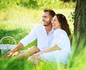 Beautiful Young Couple Having Picnic in Countryside. Happy Family Outdoor. Smiling Man and Woman rel