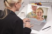 image of video chat  - Woman In Kitchen Using Laptop  - JPG