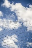 image of chicken-wire  - fluffy clouds in blue sky behind chicken wire - JPG