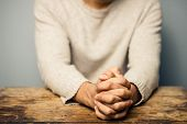 stock photo of praying  - Praying Man At Desk with his hands folded - JPG