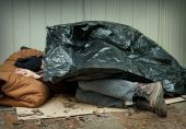 image of tarp  - Homeless man curled up under a plastic tarpaulin asleep on the street - JPG