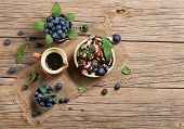 stock photo of vanilla  - Blueberries and vanilla ice cream with chocolate sauce and mint on an old rustic wooden table with copyspace top view - JPG