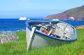 pic of old boat  - Old fisherman boat on the shore with iceberg in background Newfoundland and Labrador Canada - JPG