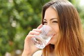 picture of water well  - Happy healthy woman drinking fresh water from a glass outdoor with a green background - JPG