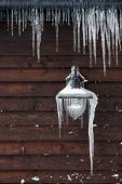 Icicles Hanging From A Lamp And Drainpipe poster