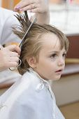 stock photo of barbershop  - Cute innocent boy at barbershop looking astonished - JPG