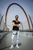 foto of turin  - Handsome young man standing outdoors in front of Olympic Arch in Turin Italy - JPG