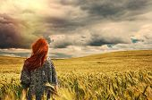 stock photo of storms  - fashion young red hair woman standing back outdoor on breathtaking view of dramatic storm sky in the field - JPG