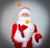 stock photo of juggling  - Funny Santa Claus is juggling with tangerines - JPG