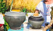 foto of stew pot  - On the table are cooked in cast iron pots boiled corn stewed potatoes bagels samovar to greet guests at the party under the open sky - JPG